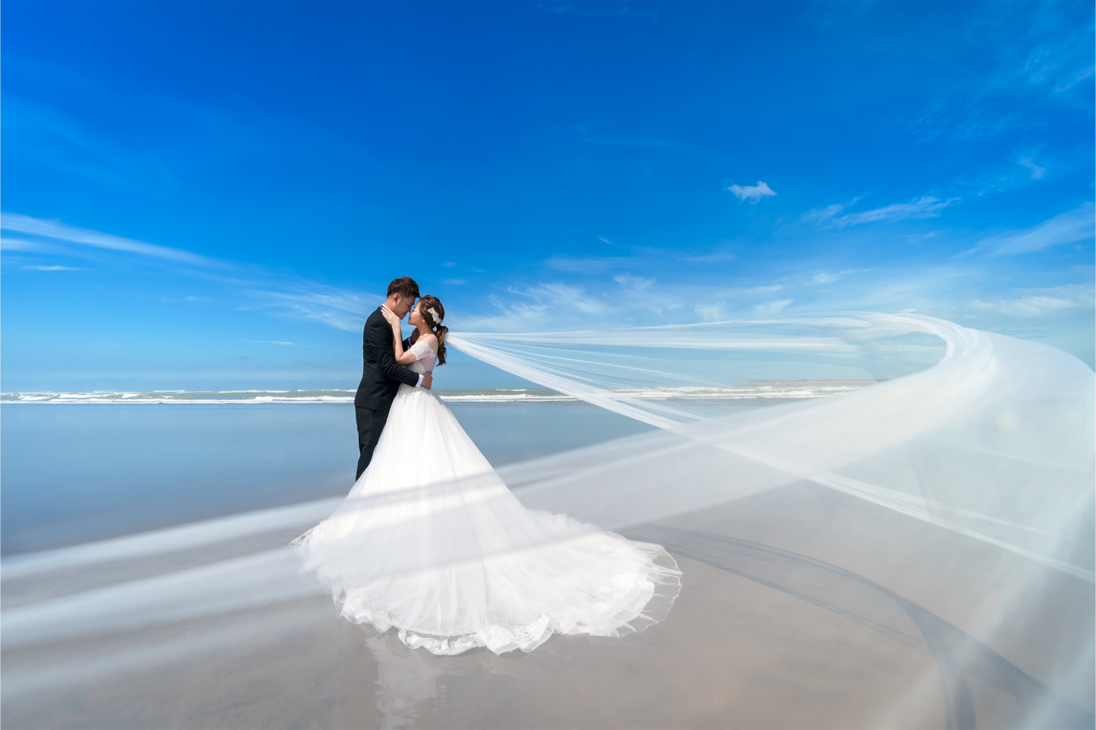 wedding couple standing by ocean with wedding veil moving in wind alpha 9