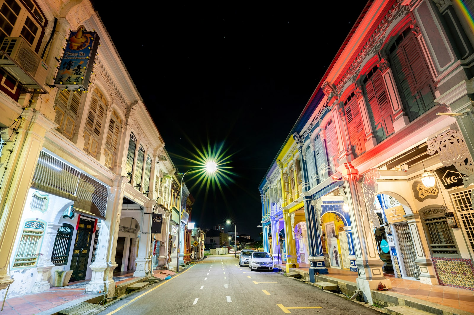 Street lined with colorful shophouses at dusk in George Town