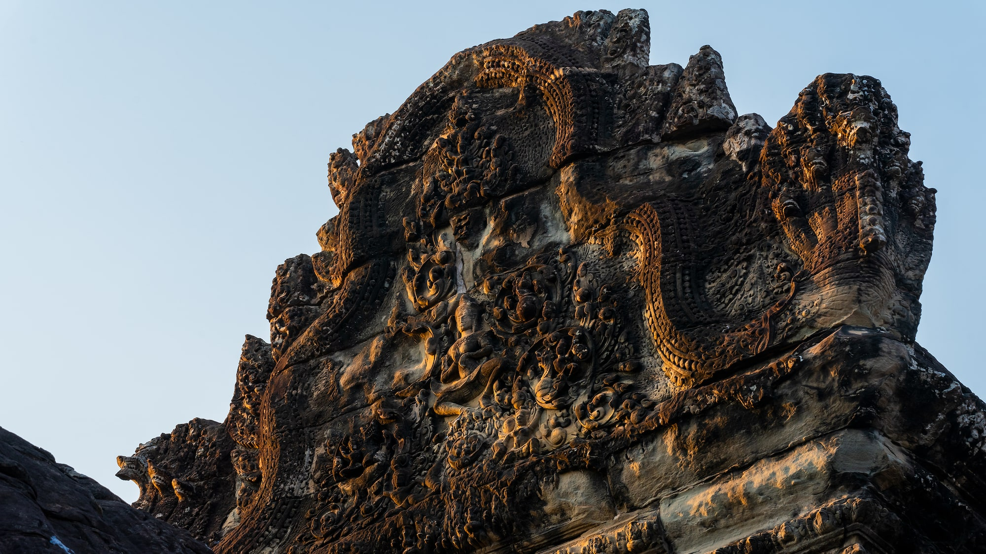 Stone carvings of ruins on stone arch in Angkor Wat