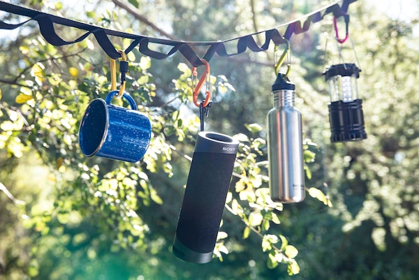 SRS-XB23 hanging from carrying strap outdoors by trees.