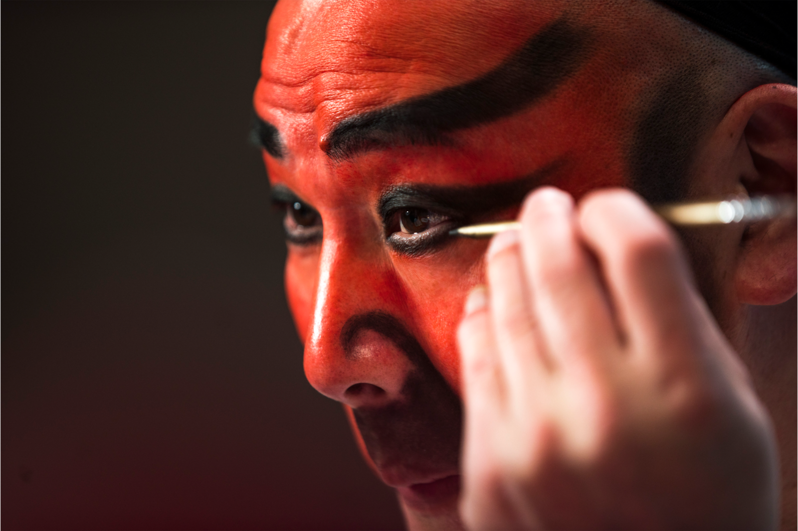 male performer in red face paint applying makeup alpha 7RII