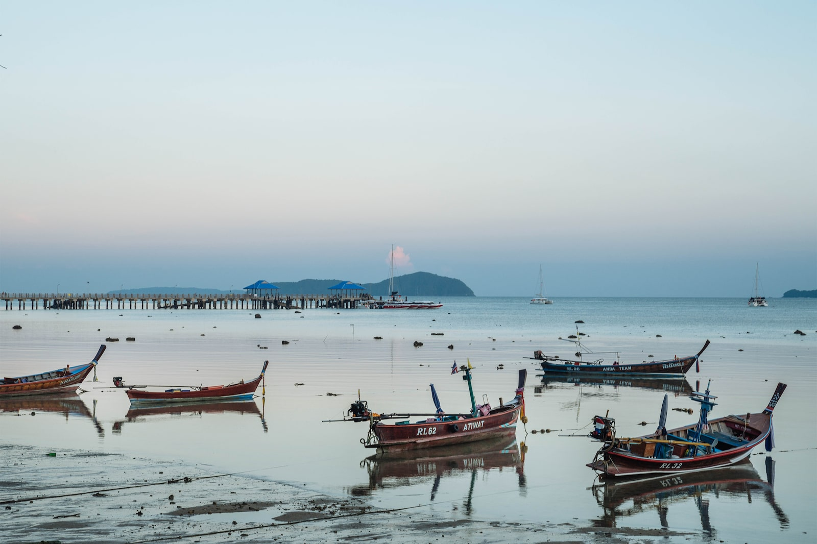 Multiple sampans resting by Phuket sea with an island in the distance