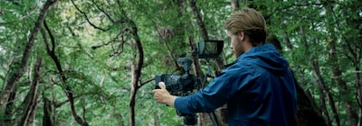 Image of a man using a camera attached to an external microphone and an external monitor, with foliage in the background