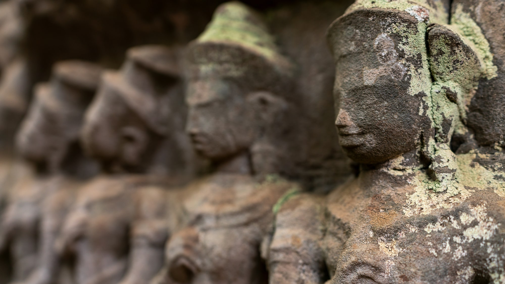 Line-up of stone statues that fades into bokeh in Angkor Wat